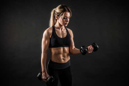 Fitness in gym, sport and healthy lifestyle concept. Beautiful athletic woman showing her trained body on black background. Bodybuilder female model training biceps muscles with dumbbell.