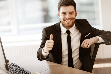Business concept. Successful young businessman at work. Manager sitting at the office table happy showing thumb up. Man smiling in suit indoors on glass window background Stock fotó