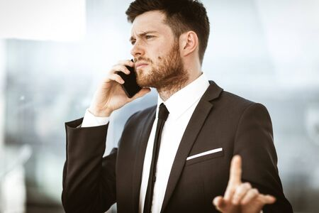 Business concept. Young businessman at the office standing and busy talking on a phone showing with hand he is resolving a very serious work problem. Man in suit indoors on glass window background Stock fotó