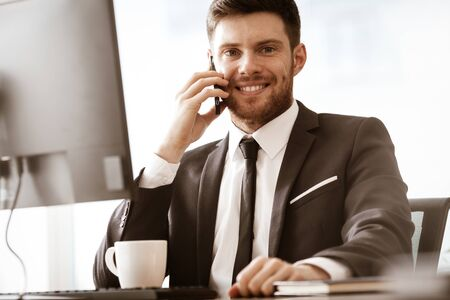 Business concept. Young businessman sitting at the office table happy talking on a cell phone getting good news about his work. Man in suit indoors on glass window background