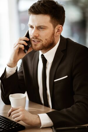 Business crisis concept. Young businessman sitting at the office table busy talking on a cell phone resolving a very serious work problem. Man in suit indoors on glass window background