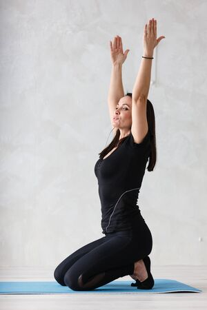Yoga meditation at home. Beautiful young woman working out in home interior, doing yoga or pilates exercises. Stock fotó