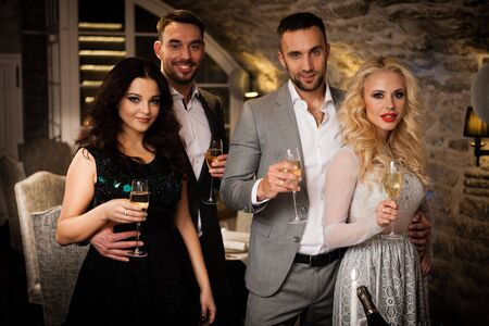 Party, holiday with friends concept. Four people with champagne glasses celebrating and toasting in restaurant. Two men and two women in elegant evening clothes, suits and dresses night out indoors