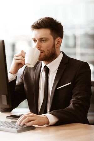 Business concept. Successful young businessman at work. Manager sitting at the office table happy drinking coffee from cup. Man smiling in suit indoors on glass window background