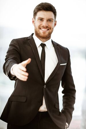 Business concept. Successful young businessman at work. Manager standing in office happy reaches out for a handshake. Man smiling in suit indoors on glass window background