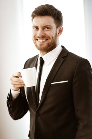 Business concept. Successful young businessman at work. Manager standing in office happy drinking coffee from cup. Man smiling in suit indoors on glass window background