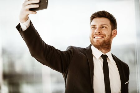 Business concept. Happy smiling young businessman at the office standing and making selfie or video chat conference using cell phone at work. Man in suit indoors on glass window background Foto de archivo - 150126457