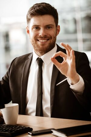 Business concept. Successful young businessman at work. Manager sitting at the office table happy showing ok sign with his hand. Man smiling in suit indoors on glass window background Foto de archivo - 150126807