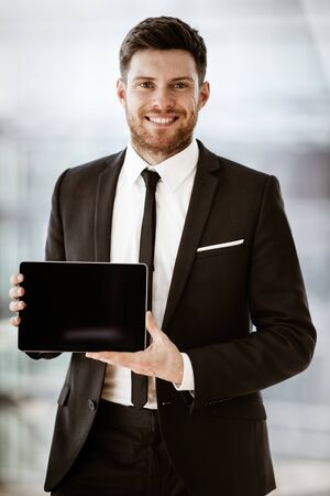 Business concept. Happy smiling young businessman standing in office demonstrating wireless touchpad tablet computer. Man in suit indoors using internet device on glass window background