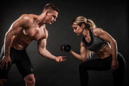 Fitness in gym, sport and healthy lifestyle concept. Couple of athletic man and woman showing their trained bodies on black background. Two bodybuilder models standing and demonstrating tight muscles. Stock Photo