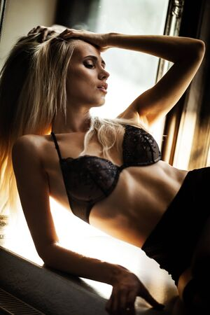 fashion and lingerie concept - beautiful blond lady portrait wearing sexy bra and panties in loft-style interior. Woman in underwear poses on a window in contrast light and shadows Foto de archivo - 150555766