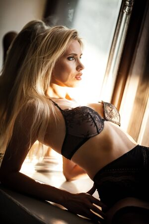 fashion and lingerie concept - beautiful blond lady portrait wearing sexy bra and panties in loft-style interior. Woman in underwear poses on a window in contrast light and shadows Foto de archivo - 150555769