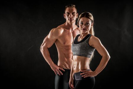 Fitness in gym, sport and healthy lifestyle concept. Couple of athletic man and woman showing their trained bodies on dark background. Two bodybuilder models standing and demonstrating tight muscles. Standard-Bild