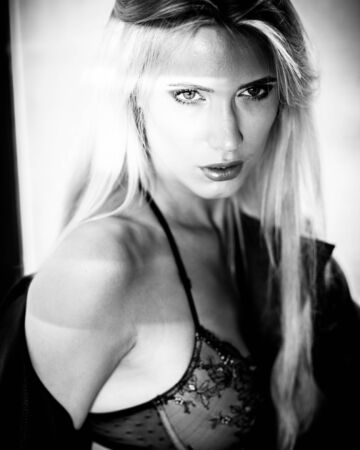 fashion and lingerie concept - beautiful blond lady portrait wearing sexy bra and panties in loft-style interior. Woman in underwear poses on a window in contrast light and shadows in monochrome. Foto de archivo
