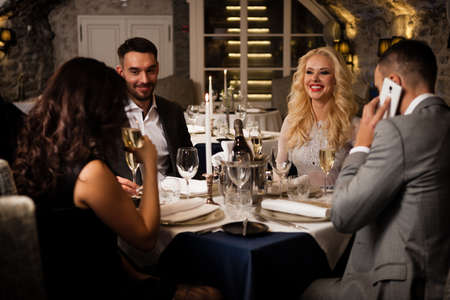 Party, holiday with friends concept. Four people with champagne glasses celebrating and toasting in restaurant. Two men and two women in elegant evening clothes, suits and dresses night out indoors.