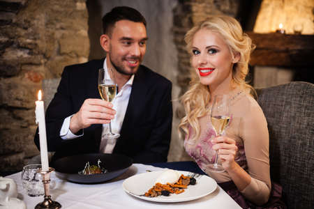 Romance and dating concept. Young couple man and woman with champagne glasses celebrating and toasting in restaurant. Two people male and female in elegant evening suit and dress on romantic dinner