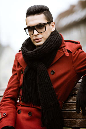 LGBTQ community lifestyle concept. Young man sits on bench in city park. Handsome fashionable male model poses in cityscape outdoors. Wears red coat, gloves, sunglasses and black scarf