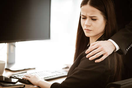 Sexual harassment at work. Male businessman puts hand on annoyed female assistant shoulder at workplace showing inappropriat behaviour. Two people man and woman conflict relations in modern office.