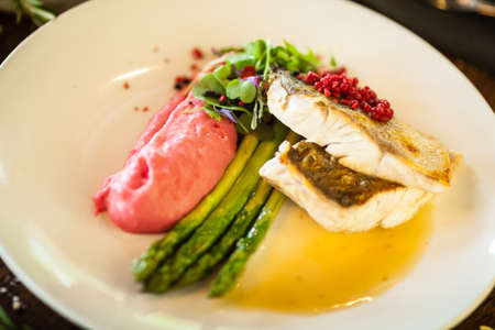 Pike-perch fillet. Asparagus, pearl couscous, white wine sauce, beet-flavored mashed potatoes. Delicious seafood fish closeup served on a table for lunch in modern cuisine gourmet restaurant
