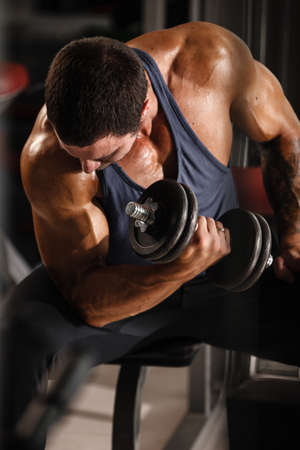 Fitness in gym, sport and healthy lifestyle concept. Handsome athletic man in blue shirt making exercises. Bodybuilder male model training biceps muscles with dumbbell