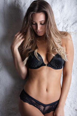 Beauty of woman body and lingerie concept. Beautiful blond female fashion model in black underwear poses indoors. Young girl stands near grey wall wearing bra and panties. Standard-Bild