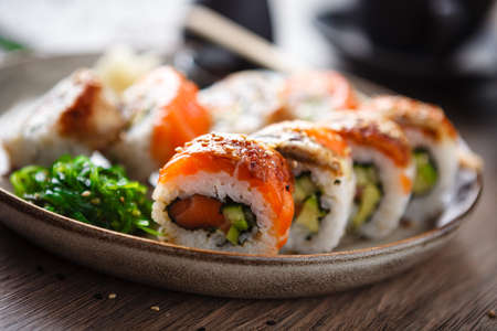 Sushi maki rolls with salmon, eel, avocado, cucumber on a plate with chopsticks, soy sauce, wasabi and ginger. Japanese traditional fish food closeup served for lunch in modern gourmet restaurant.