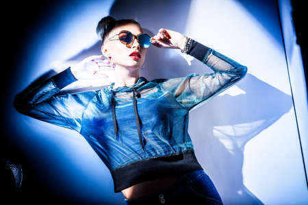 Fashion concept. Portrait of a beautiful woman in jacket with hood and sunglasses in bright mixed contrast light. Female model dances in studio. Professional makeup and colorful background.