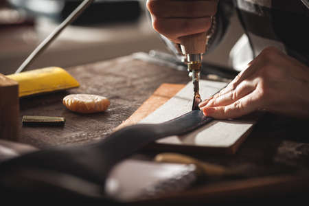 Leather handbag craftsman at work in a vintage workshop. Small business concept.