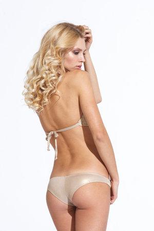 Beautiful young woman with fit trained slim body wearing swimwear bikini isolated on white background. Fashion model poses in bright studio light. Standard-Bild