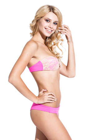 Beautiful young woman with fit trained slim body wearing swimwear bikini isolated on white background. Fashion model poses in bright studio light. Foto de archivo