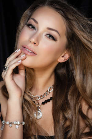 Perfect beauty and jewelry concept. Portrait of beautiful female model wearing ring, necklace and wristband on black background. Young blond woman shows glamorous finery. Stockfoto