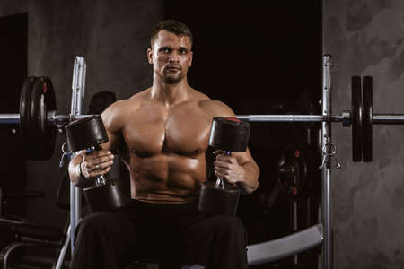 Fitness in gym, sport and healthy lifestyle concept. Handsome athletic man with torso on workout with dumbbells. Bodybuilder male model resting after hard training. Heavy barbell on background
