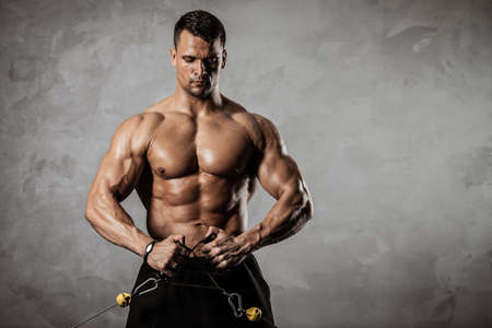 Fitness in gym, sport and healthy lifestyle concept. Handsome athletic man with torso making exercises. Bodybuilder male model pumping up muscles on crossover training apparatus