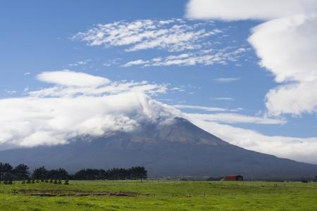 egmont: A dormant volcano Mt Taranaki, New Zealand, surrounded by green fields Stock Photo