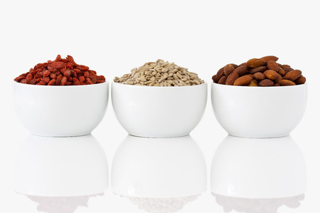 Almonds, sunflower seeds and goji berries on white background photo