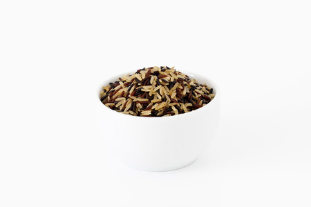 Brown, red and black rice mix in a bowl on white background photo