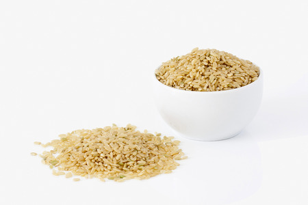 Brown rice on white background photo