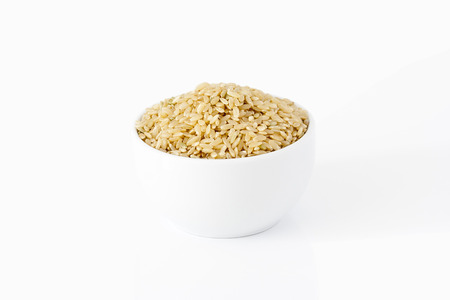 protein crops: Brown rice in a bowl on white background
