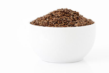 Flaxseeds in a cup on white background photo
