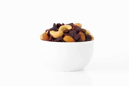 Healthy snack of dried fruits in a bowl on white background photo