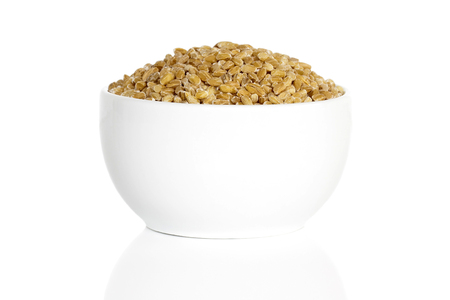 barley seeds: Pearl barley seeds in a cup isolated on a white background.