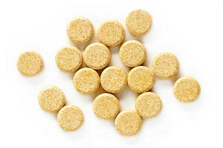 A pile of vitamin C supplement tablets isolated on a white background.