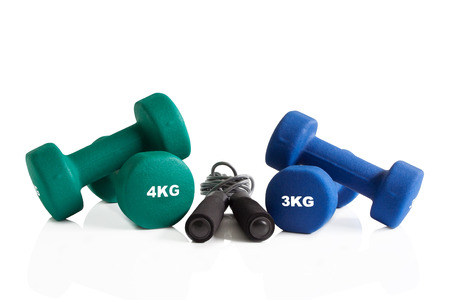Green and blue dumbbells with a skipping rope isolated on a white background.