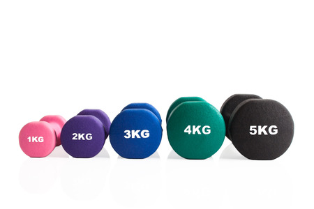 A line of gym dumbbells for training isolated on a white background. Stok Fotoğraf