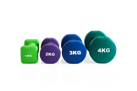 Isolated colorful dumbbells lineup on a white background. Stok Fotoğraf