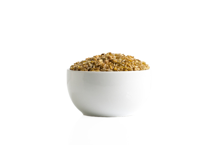 Brown freekeh in a cup isolated on a white background.