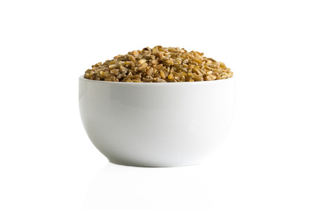 Brown freekeh grains in a cup isolated on a white background.