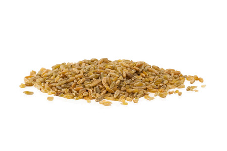 Stack of uncooked freekeh grains on white background. Stok Fotoğraf