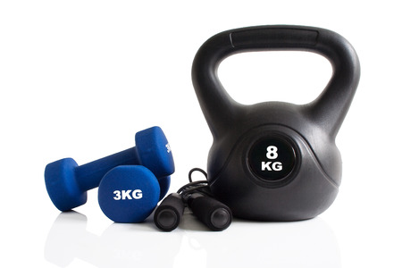 Kettlebell, dumbbells and skipping rope set for a fitness training isolated on a white background.