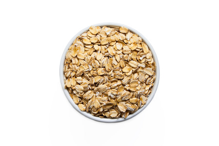 Uncooked oats in a cup, isolated on a white background. Stok Fotoğraf